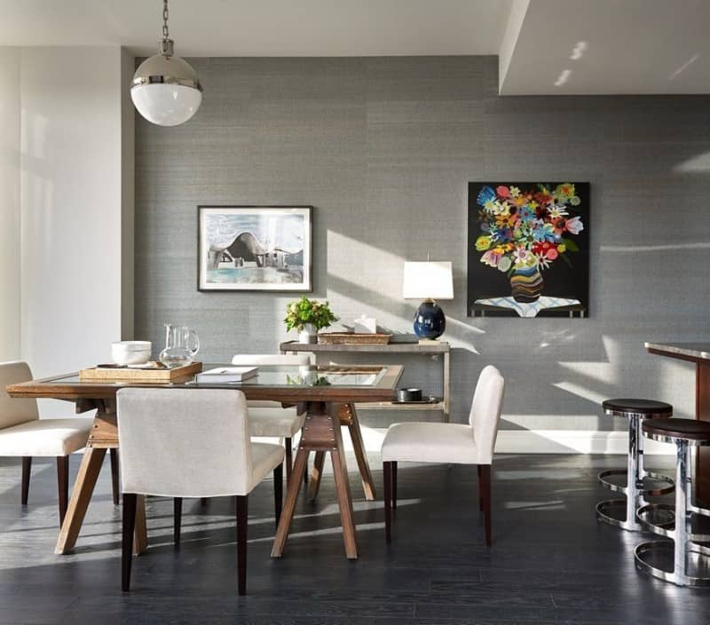 A gray dining space designed with wall canvas and frame along with a globe pendant light. It includes a glass top dining table framed with wood and white chairs over dark hardwood flooring.