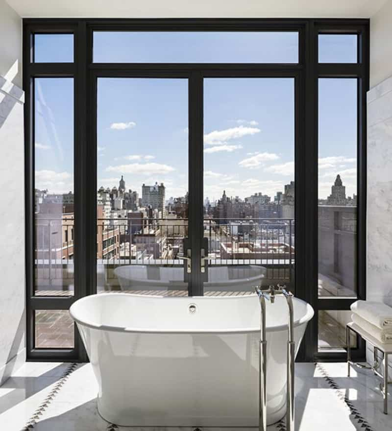 This master bathroom offers a freestanding tub near the doorway leading to the private balcony.
