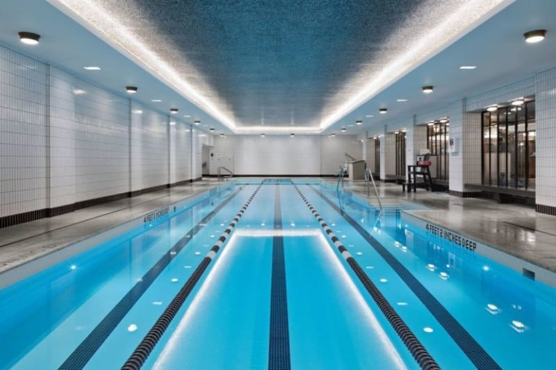 Large indoor swimming pool featuring a stunning long pool and a tray ceiling.