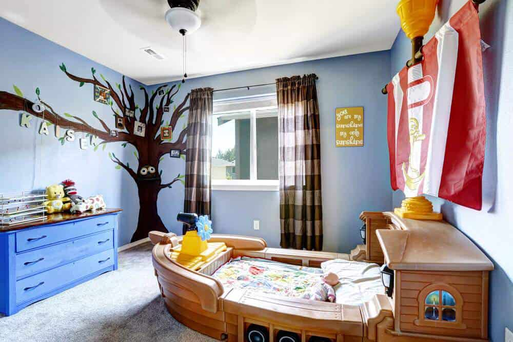 The small boat in this mid-sized carpeted room makes a fun bed for wannabe sailor. The rest of the décor has been kept neutral yet stylish featuring a mural family tree painting, small cabinetry, sliding window and purple wall paint color.
