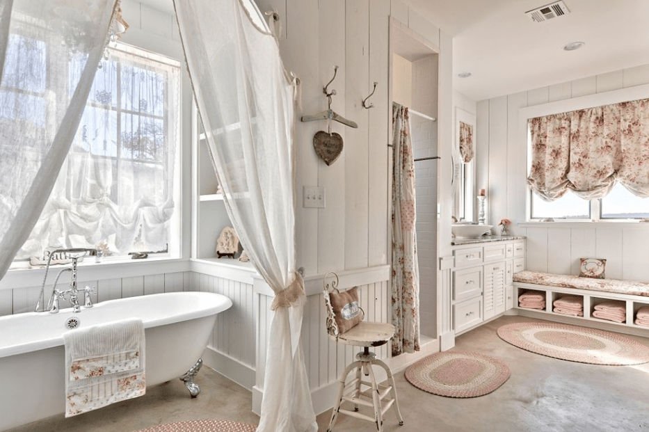 Airy bathroom with a walk-in shower and clawfoot tub beneath glass windows wrapped with sheer curtains. It includes a window seat nook fitted with a floral pink cushion that matches the draperies.