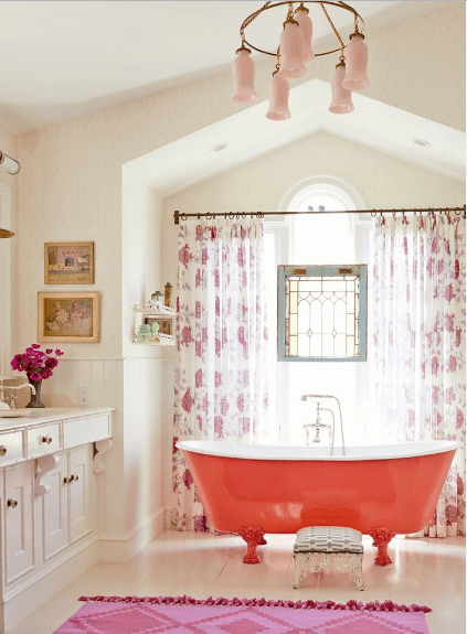 The gorgeous bathroom offers a red freestanding bathtub with a patterned stool lighted by a lovely pink chandelier and natural light that streams through the glass window covered in floral draperies.