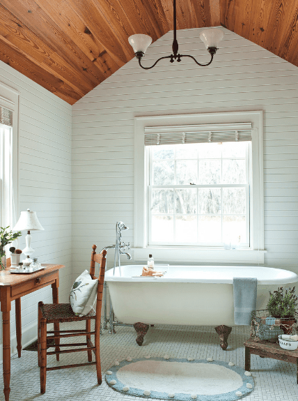 Bathroom with white shiplap walls and wood vaulted ceiling with a hanging vintage pendant. It has a clawfoot tub over patterned floor tiles topped with a blue oval rug.