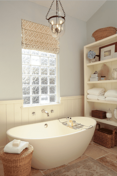 Cottage style bathroom showcases a soaking tub underneath a glass block window dressed in a patterned roman shade.