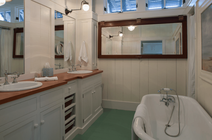 This bathroom offers a dual sink vanity with a wood countertop paired with frameless mirrors and lighted by wrought iron sconces across a freestanding bathtub.