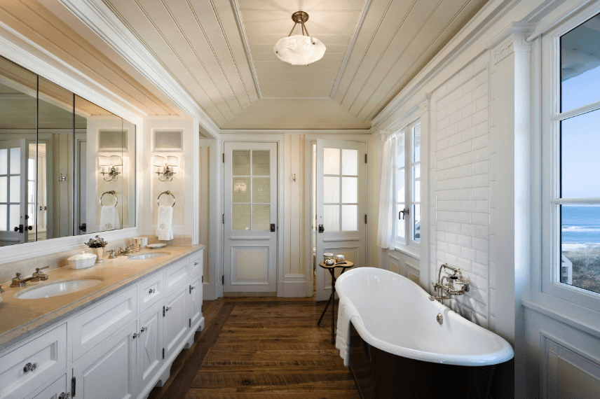 Hallway bathroom features a black bathtub over hardwood flooring. It includes a white dual sink vanity topped with marble counter.