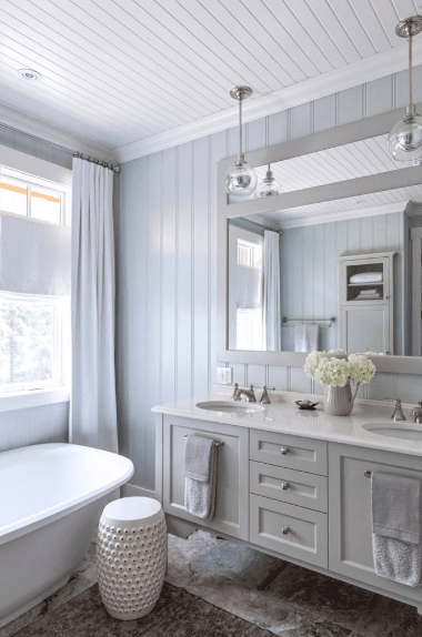 A pair of glass pendants illuminate the floating dual sink vanity mounted on the muted blue beadboard wall in this fresh bathroom. It is paired with a white perforated stool placed beside a bathtub.
