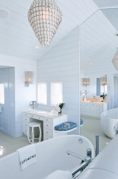 White bathroom showcases a vanity with white stool adjacent to the soaking tub illuminated by a shell chandelier.