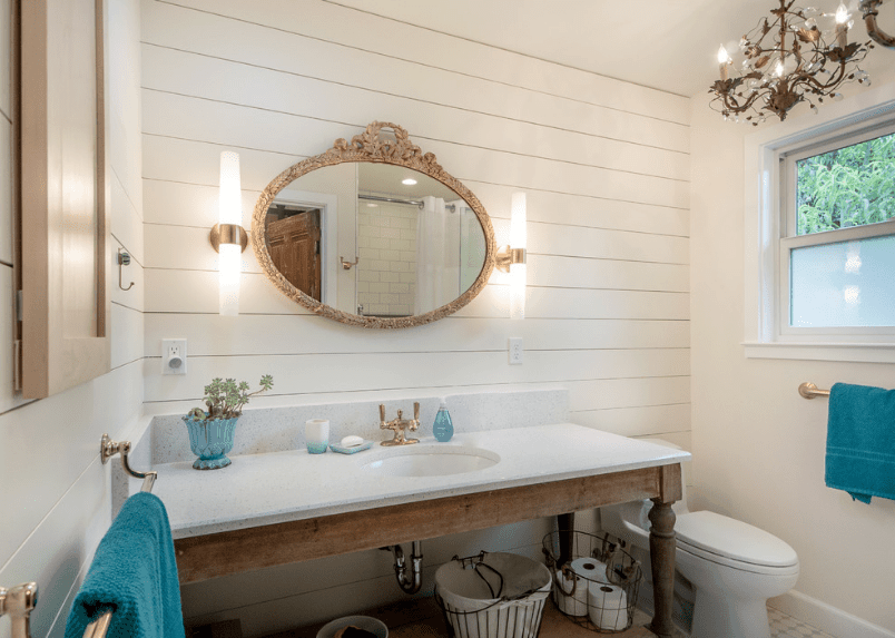 Bathroom with a vintage feel from the chandelier, faucet and ornate mirror mounted on the white shiplap wall.