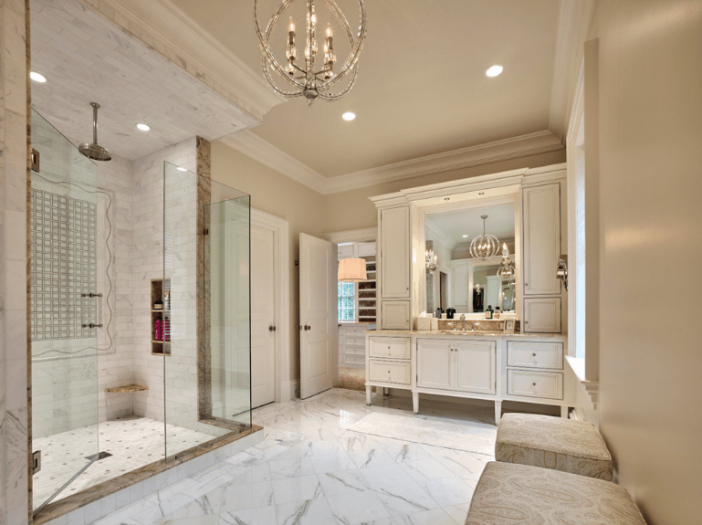 Spacious bathroom boasts a white sink vanity and a walk-in shower with subway tiles enclosed in glass. It is illuminated by a fancy candle chandelier and recessed lights mounted on the beige ceiling.