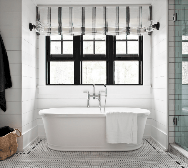 Cottage style bathroom boasts a freestanding bathtub beneath a black framed glass window covered with a striped roman shade.