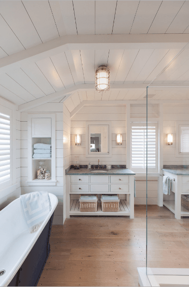 Simple bathroom surrounded with white shiplap walls and vaulted ceiling. It has a white sink vanity topped with black granite counter and paired with a medicine cabinet.