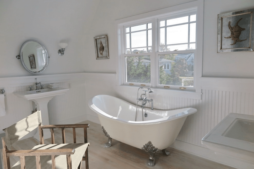 The classic bathroom features a pedestal sink with mirror and a clawfoot tub accompanied by a rustic wooden chair.
