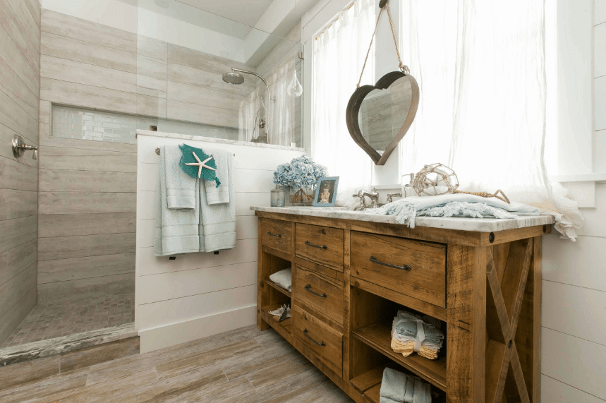 Bathroom with a walk-in shower and distressed wood vanity with marble countertop paired with a heart-shaped metal mirror mounted in between windows.