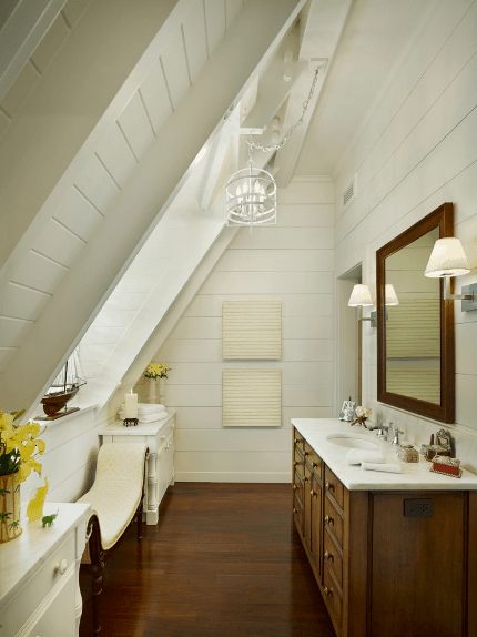 Narrow bathroom offers a white Cleopatra bench underneath a window fixed to the vaulted shiplap wall. It includes a dark wood vanity over rich hardwood flooring.