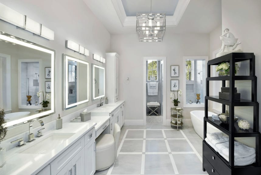 Modern bathroom features a dual sink vanity that runs the length of the room. It has three mirrors lighted by horizontal sconces and a white chair over marble flooring.