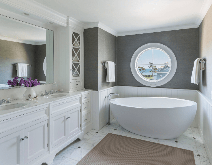 This bathroom showcases a soaking bathtub underneath a round window fitted on the gray wall and a dual sink vanity topped with a white marble counter that complements with the flooring.