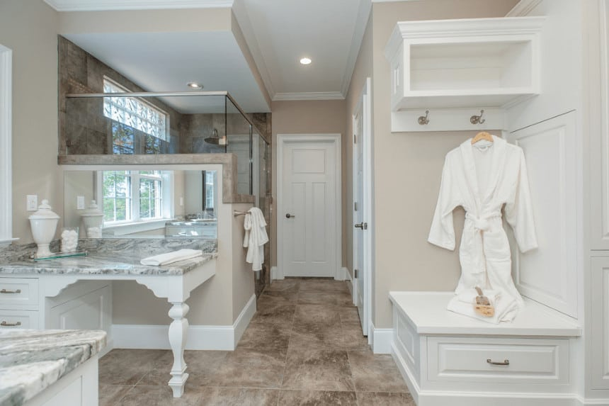 The traditional bathroom offers a walk-in shower and vanity with gray marble countertop and frameless mirror. It includes storage and shelf with hooks on the corner.