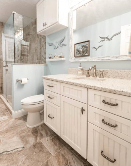 Blue bathroom with a white sink vanity topped with granite counter along with wall storage and floating shelf above the toilet.