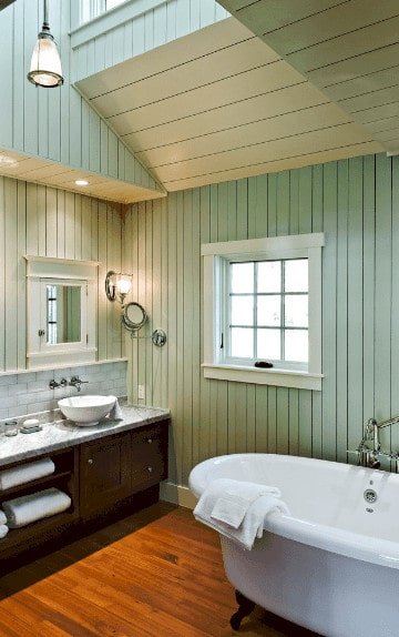 Cottage style bathroom boasts a freestanding bathtub and vessel sink vanity with gray marble countertop and white brick backsplash.