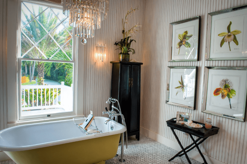 This bathroom is designed with framed floral wall arts mounted on the beadboard wall. It has a yellow freestanding tub illuminated by a glass chandelier and sconce.