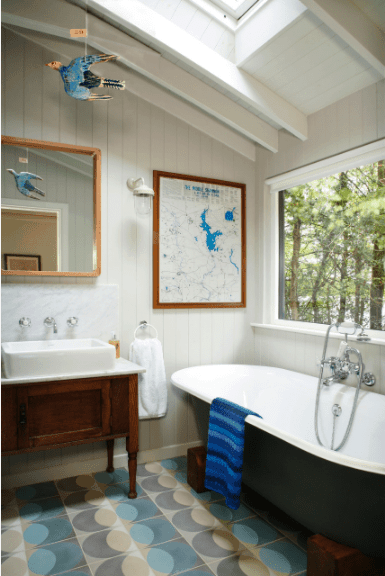 Small bathroom accented with a blue patterned tiled flooring. It includes a vessel sink vanity and black soaking tub with chrome fixtures.