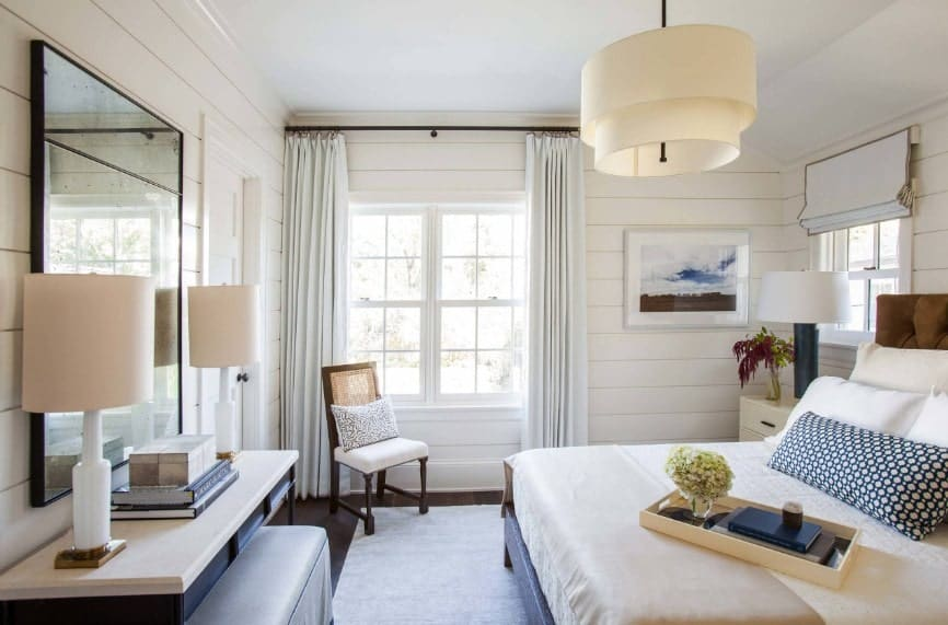 Primary bedroom boasting a classy bed along with a built-in desk in front lighted by table lamps. The room also features a charming ceiling light.