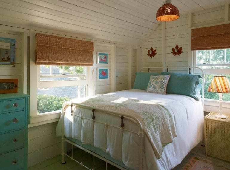 A focused shot at this primary bedroom's comfy bed surrounded by white walls, hardwood floors and a wooden ceiling.