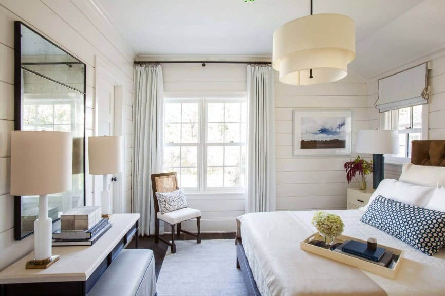 Spacious primary bedroom featuring a large elegant bed along with a built-in desk in front lighted by two table lamps. The room also features a charming ceiling light.