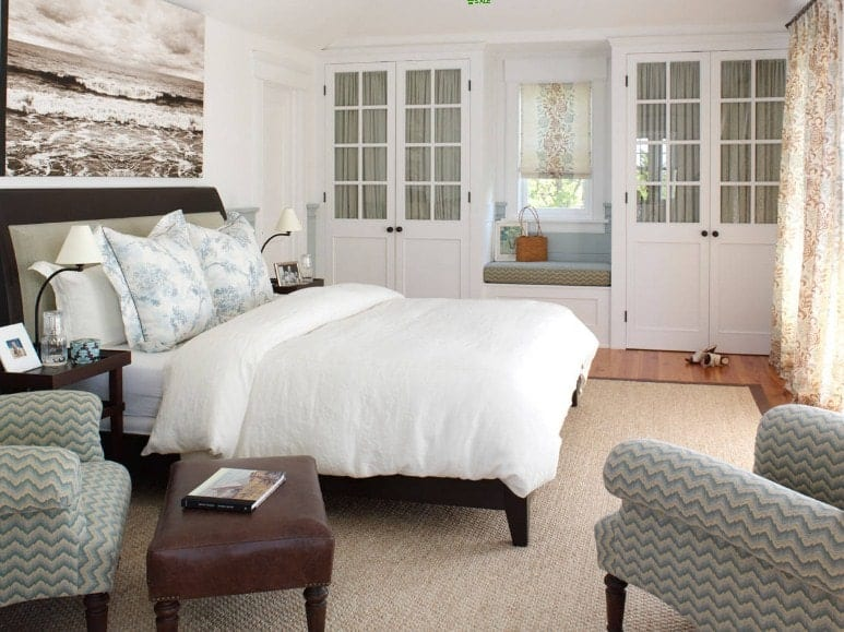 Primary bedroom featuring a large cozy bed along with a sitting area with two beautiful chairs on the side.