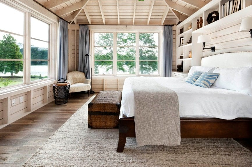 Spacious primary bedroom featuring wooden walls and hardwood flooring, along with a wooden ceiling. The room has a large bed and has multiple built-in shelves.