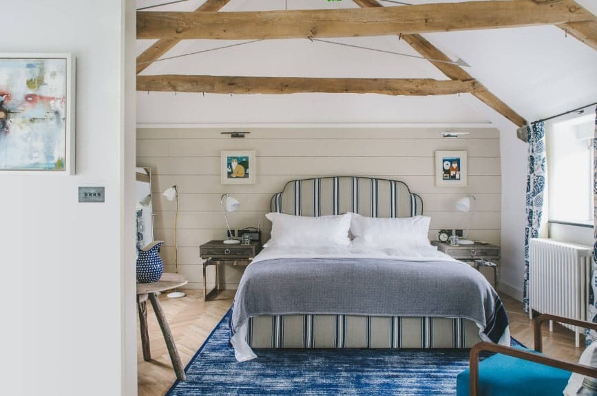 Large primary bedroom featuring a classy bed set on top of a stylish blue area rug covering the herringbone-style hardwood flooring.