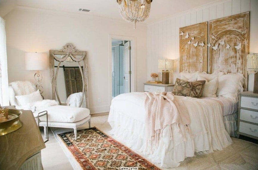 Primary bedroom boasting an elegant bed set lighted by two classy table lamps and a glamorous chandelier. The room also has its own bathroom.