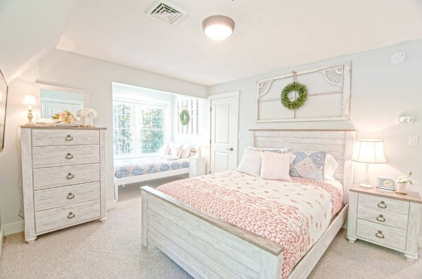 Bright primary bedroom featuring thick carpet flooring along with white walls and ceiling. The room offers a rustic bed frame along with other rustic furniture.
