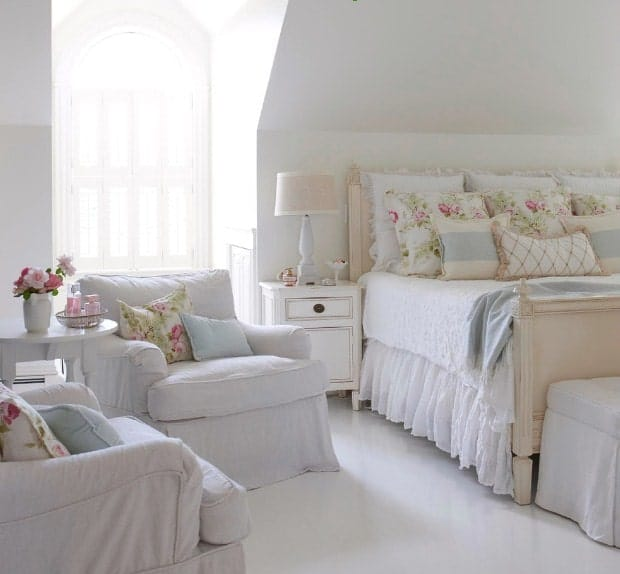 White primary bedroom featuring white flooring and white walls. The room offers a large lovely bed along with two white seats on the side with a small center table.
