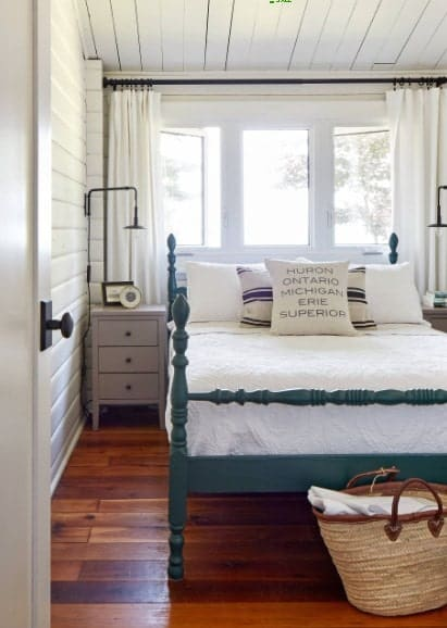 A focused shot at this primary bedroom's bed set near the windows. The room features hardwood flooring and a wooden ceiling.
