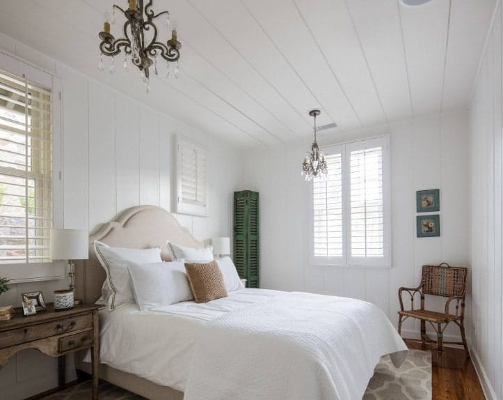 This primary bedroom features a classy bed setup lighted by two gorgeous chandeliers and is surrounded by white wooden walls and ceiling.