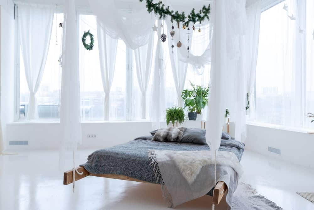 A focused shot at this primary bedroom's stunning bed setup with indoor plants, surrounded by white walls and floors, along with white curtains.