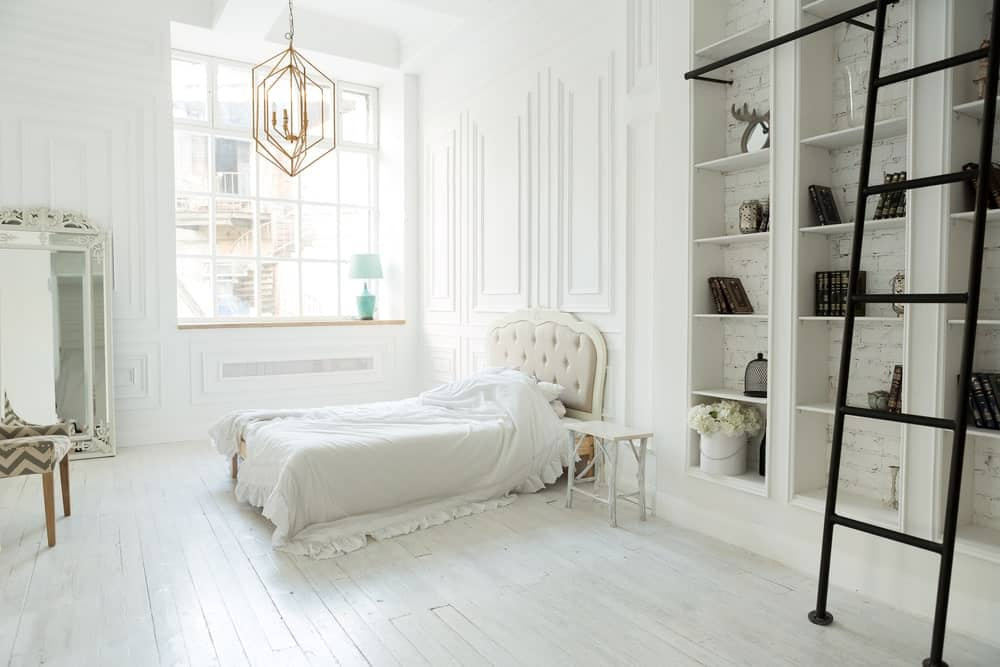 Large primary bedroom with a tall ceiling and white walls. The room has a charming bed setup lighted by a gorgeous ceiling light. The room also offers built-in shelves.
