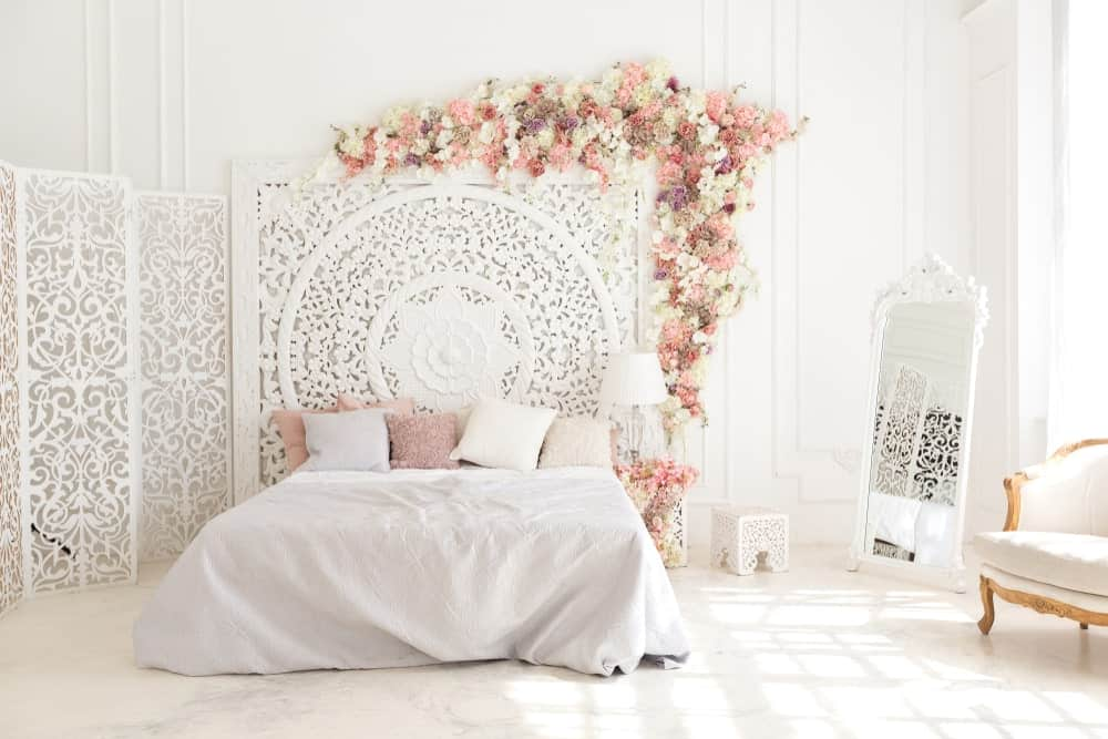 A focused shot at this primary bedroom's lovely bed setup surrounded by white walls and white decors that makes the room so bright.