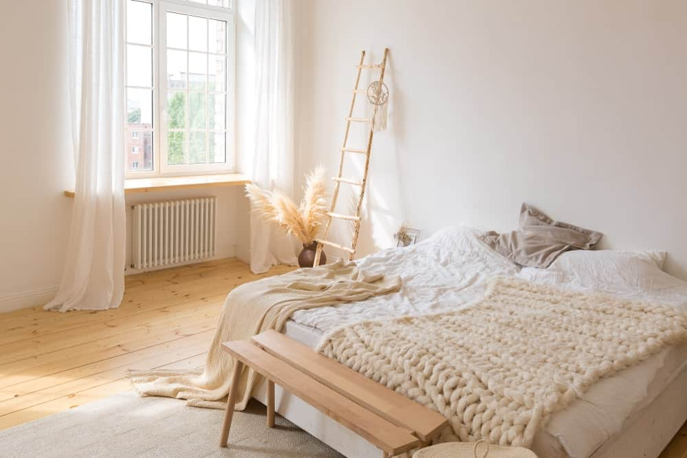 A focused shot at this primary bedroom's large bed set on the hardwood flooring. The glass window on the side features lovely white window curtains.