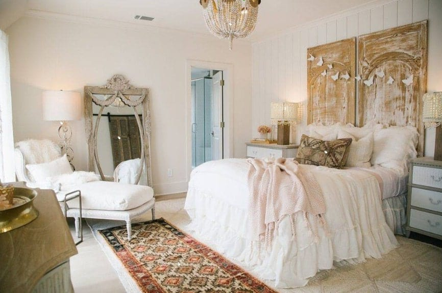 Primary bedroom boasting an elegant bed set lighted by a glamorous chandelier. The room also has its own bathroom area.
