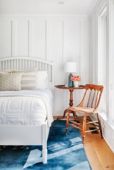 This primary bedroom offers a large white bed matching the white walls and white ceiling. The hardwood flooring is topped by a stylish blue area rug.