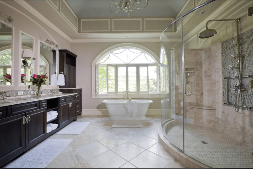 A dark wood storage cabinet and dual sink vanity stand out in this country style bathroom with arched window and marble tile flooring topped by white shaggy rugs.