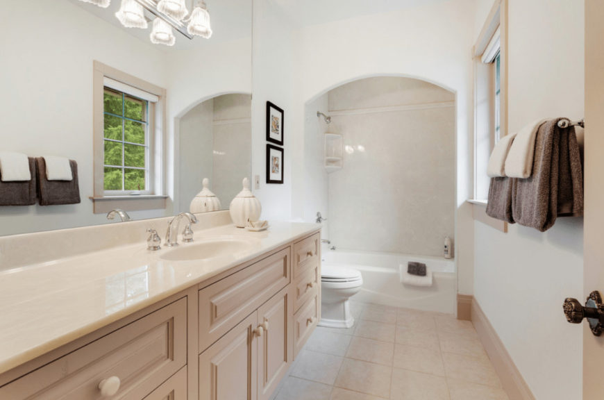 Fresh bathroom decorated with black framed wall arts that hung over the toilet placed in between a light wood vanity and shower and tub combo with an alcove design.