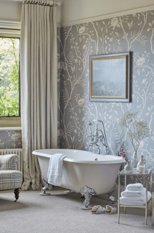 Clad in gorgeous floral wallpaper, this bathroom features a clawfoot tub accompanied by a checkered seat and metal side table over carpet flooring.