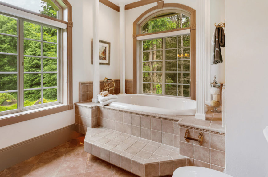 Airy bathroom with a deep soaking tub lined with white columns and framed glass windows overlooking the lush outdoor greenery.