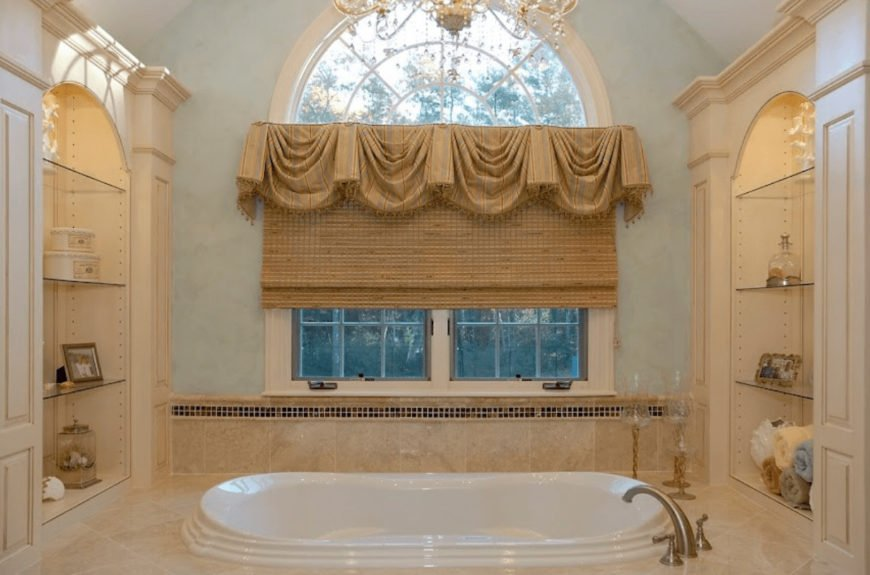 This bathroom boasts a drop-in tub flanked by arched inset wall niches that are fitted with glass shelves. It is illuminated by a crystal chandelier and natural light from the picture window dressed in classy valance and wicker roman shade.