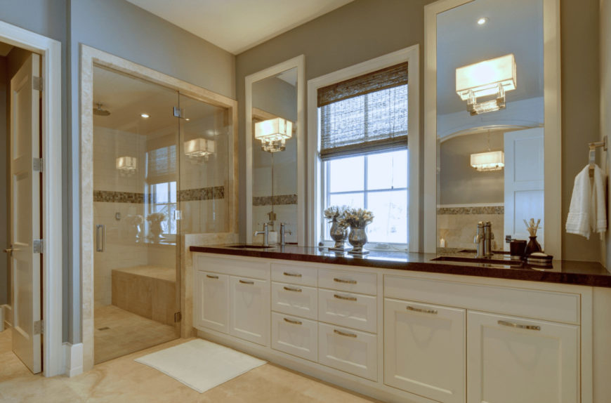 Country style bathroom offers a walk-in shower with tiled bench and a black granite top vanity with white framed windows mounted with glass sconces.