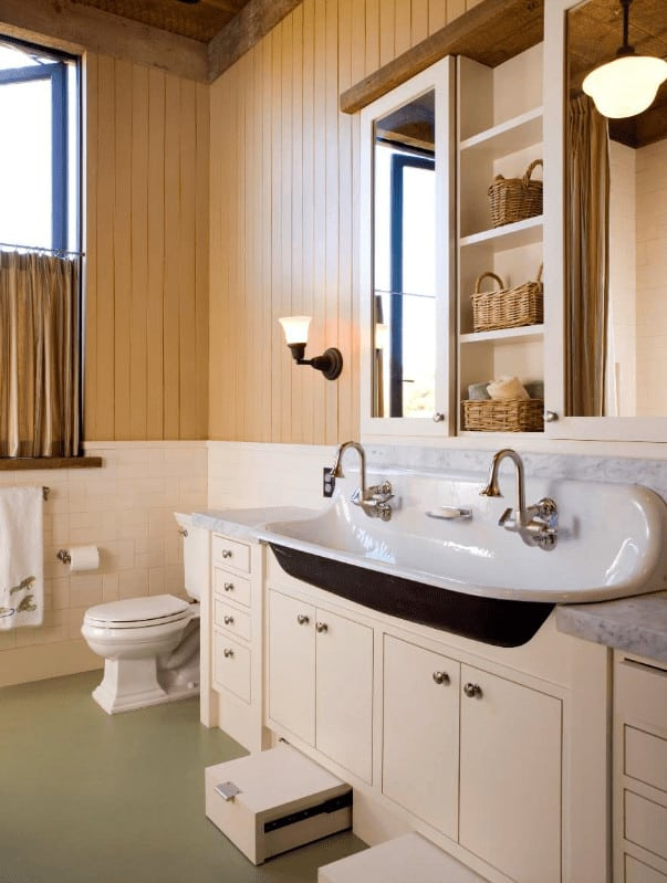 This bathroom features a white sink vanity paired with mirrored medicine cabinets and built-in shelves filled with rattan baskets. It is illuminated by a pendant light and wrought iron sconce mounted on the beadboard wall.